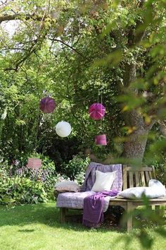 Purple throw, paper lanterns, and pillows under a shady tree...