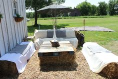 Straw bale seating outside the barn for wedding reception. Bales are topped with thrift store blankets & pillow shams. Table made of pallet and straw bales. Umbrella I found in a  garbage bin at curb side! Free mulch from a tree removal company.