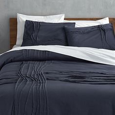 monochromatic merge. Navy-on-navy sleepscape dreams up tone-on-tone texture. Woven of soft cotton/linen, flowing ribbons of fabric cross paths off-center in an organic ripple effect. Duvet and matching shams reverse to solid navy. Duvet has non-slip corner ties and hidden button closure. Shams are finished neat with envelope closures.