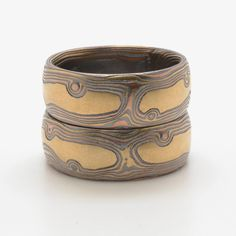 These 8mm matched bands are shown in the Woodgrain pattern and the Oxidized Fire metal combination with an etched and oxidized finish and a low-dome profile. The Fire palette features 14k yellow gold, 14k red gold and sterling silver. All mokume rings are custom made on demand, buy this