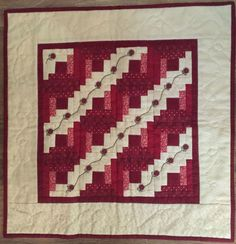 """Little Red Thirteen is 18"""" square and features log cabin blocks in reds and creams. An embroidered vine runs through the light areas with 1/2"""" red flower buttons.The pattern includes the packet of buttons.The kit includes all the fabrics for the top, back, and binding, along with the pattern and buttons and the green embroidery floss. Small Quilts, Mini Quilts, Quilting Tips, Quilting Designs, Embroidery Patterns, Quilt Patterns, Patchwork Cards, Miniature Quilts, Doll Quilt"""