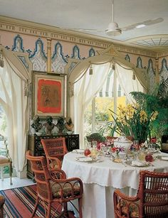 Renzo Mongiaardino tempered his characteristically bold palette with an airier one in the late 1980s for a villa near Rome's Appian Way owned by fashion designer Valentino. The stenciled walls and ceiling of the dining room were inspired by an 18th-century Sicilian veranda.  Photography by Derry Moore, Robert Emmett Bright