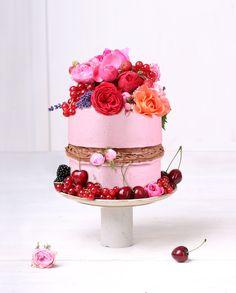 Eine Erdbeer Rohkostcreme mit gebackenen Schokoladenböden und Mousse au chocolate. Mit Blumen und Früchten dekoriert.