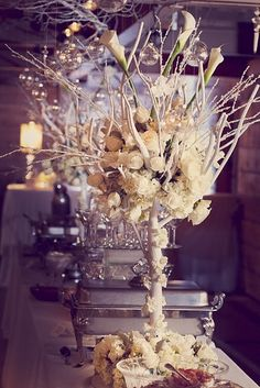 A statment table display made up of roses, lilies and branches sprayed white..