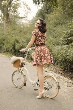 Old school bike... love the chic style of the girl contrasting with the overgrown roadside.
