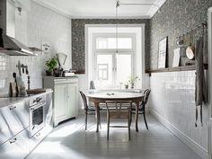 15x15cm glansigt vitt kakel, en hyllist som löper längst hela köket och ovanför listen tapeten Pimpernel från William Morris