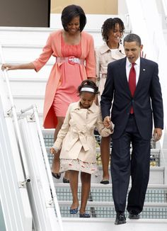 http://www.revelist.com/influencers/sasha-and-malia-obama-style/1013/Chic matching trenchcoats as they land in Moscow in summer, 2009./6