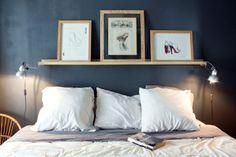 Une tête de lit avec des cadres sur un mur sombre