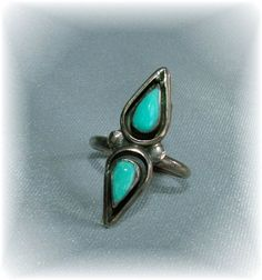 A very lovely vintage ring in unmarked (common in Native American vintage jewelry) silver with two gorgeous tear drop turquoise stones. Native American design, signed JW. Simple shadowbox settings with smooth bezels.