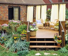 Putting It All Together: A little of everything gave this deck new life. Easy-care perennial plantings around the base of the deck really help to dress it up. Cleaning it and adding a new coat of deck stain helped keep it from feeling dated. Sheets of outdoor-friendly fabric provide cooling shade on hot summer days and add a bit of privacy so your neighbors won't have to know what you're eating for dinner every night.