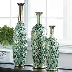 This dazzling long-neck vase is ready to strut its style on your mantel, table or shelf. Its beautiful peacock design is highlighted by shimmering gold touches and turquoise jewels that sparkle and shine.