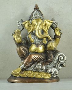 Antique Brass and Copper Ganesh Statue. • We love Ganesh - the chubby, gentle, wise, elephant-headed deity, known as the remover of obstacles. • Ganesh, or Ganesha, son of Lords Shiva and Parvati, is the deity whom worshippers first acknowledge when visiting a temple. • We love this intricate statue of Ganesh with fine detailing and each piece is individually cast of heavy recycled brass and detailed with a fine antique patina finish. • Ganesh is associated with Om, is the patron of…