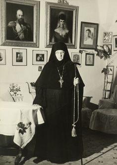 Princesa Tatiana Constantinovna, em 1958. Ela está em pé com a mão direita apoiada sobre a mesa ao lado dela para a esquerda. Ela está vestindo um hábito escuro, véu e um crucifixo. Ela está segurando uma vara longa e contas do rosário em sua mão esquerda. Há fotografias de família na parede atrás dela, incluindo grandes retratos emoldurados de Alexander III e sua consorte Maria Feodorovna. Ela deixou a Rússia após a Revolução e, eventualmente, tornou-se freira assumiu o nome Mãe Tamara.