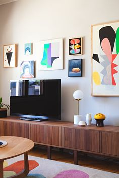 tv on sideboard with other items and art on the wall behind/around it.