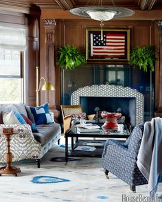 A framed American flag hangs over the Atelier Jouvence black-granite mantel in the library of a Michigan lake house.