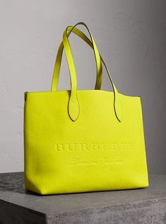 A versatile tote bag by Burberry in a vibrant neon tone, with an interior zip pocket for small essentials. The minimalist design is finished with embossed Burberry lettering and hand-painted edges.