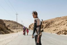 Runak Bapir Gherib, a 14-year-old from Shengal, makes her way down the Sinjar mountains after seven days. She is with her mother and sister (in the back) waiting for a car to drive them away. She took the gun from Shengal to protect her family.