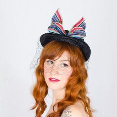 An adorable hat with a body of deep navy straw. The hat features a kepi crown and squared-off brim with veiling spilling over the edge. A