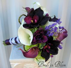 This Wedding bouquet has class and elegance. The real touch calla lilies & orchids are soft to touch and look so real, you are sure to love them. Bouquet is designed with 8 eggplant & white calla lilies, 4 plum orchids, hydrangea, lavender & plum delphinium, framed with curly willow loops and grass. Handle treatment is wrapped with a plum satin overlay ribbon and a white satin ribbon sash, completed with a sparkling rhinestone buckle.  Pictured bouquet measures 8 ( 20 cm ) wide x ...
