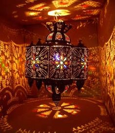 "An exotic rustic metal hanging lamp made in the souk of Marrakesh by master artisan. All handmade and hand hammered. This unique hanging lamp will give a special tone and ambiance to any room. Only when lit in a darkened room can their beauty be truly appreciated. Light filters through intricate cutwork patterns and coloured glass, and creates a beautiful ""starry"" canopy.  It measures 22"" high x 16"" wide"