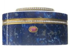 A LAPIS LAZULI, MOTHER-OF-PEARL AND DIAMOND BOX   The carved lapis lazuli box inlaid with a mother-of-pearl scene depicting a man and a woman, enhanced by a circular-cut diamond and gold trim, with a cabochon ruby clasp