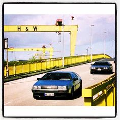 Belfast 1981. Delorean cars leaving the factory with the famous Harland & Wolff Cranes in the backdrop