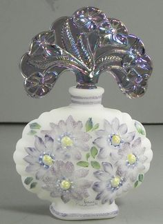"'Fenton Hand Painted Art Glass Perfume Bottle Carnival Stopper'  Designer ~Bill Fenton~  [White satin glass bottle, hand painted purple flowers, amethyst carnival stopper. Signed by the artist, and the bottom is marked New Century Collection Glass Artistry for the New Millenium, Bill Fenton. 6"" tall.]"