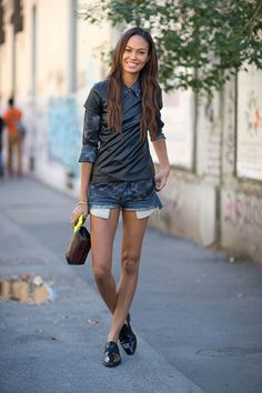 Milan Fashion Week spring 2014, Street style. Joan Smalls in cool, layered outfit: Cut-off jeans shorts, dark camo shirt, shiny polyester t-shirt, shiny flats.