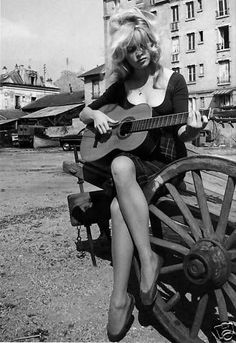 """talesfromweirdland: """" Brigitte Bardot playing guitar on location. Circa She pioneered the """"messy hair"""" look, which was uncommon at the time: women were expected to look sophisticated,. Brigitte Bardot, Bridget Bardot, Golden Age Of Hollywood, Classic Hollywood, Old Hollywood, And God Created Woman, Intimate Photos, Serge Gainsbourg, Photo Vintage"""