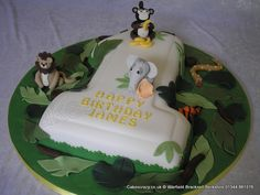 Jungle Animal Number One Cake. Large number 1 numerical shaped birthday cake with a jungle animal theme. Topped with hand crafted sugar models (monkey lion elephant tiger and snake). Decorated with foliage leaves Number One Cake, Number Cakes, Jungle Animals, Jungle Safari, Birthday Party Themes, Birthday Cake, Safari Cakes, Sugar Craft, Cupcake Cakes