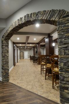 This is one HUGE basement! The details needed to be bold so they wouldnt get washed out. I love the large stack stone archers and stained beams! #TeamGREEN #barndoors #stackstone #arch #LVT # customcarpentry #greenbasementsandremodeling
