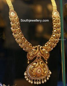 22 Carat gold antique peacock nakshi mango haram adorned with rubies, emeralds, cz stones and south sea pearls by Sree Kumaran Thangamaligai Jewellers. Gold Temple Jewellery, Gold Jewellery Design, Gold Jewelry, Antique Jewelry, Initial Necklace Gold, Schmuck Design, Indian Jewelry, South Indian Bridal Jewellery, Bridal Jewelry