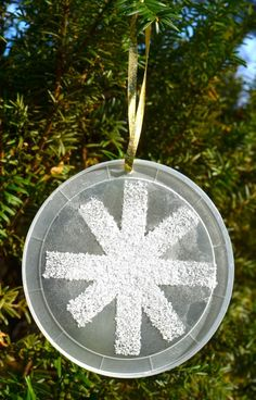 Easy snowflake ornament for kids to make. Double sided tape, salt, clear lid.