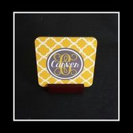 Elegant monogrammed set of 4 coasters. Pictured coaster has a gold quatrefoil background accented with a gray circle frame. The font is a vine initial with complementary last name.