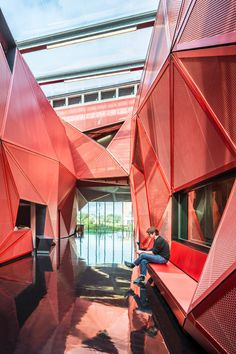 Faceted Red Metal Creates Sculptural Facade For Music Centre by Périphériques on Triangular facets of perforated red metal frame the entrance to this cultural centre, completed by Paris studio Périphériques for a town in northwest Folding Architecture, Facade Architecture, Contemporary Architecture, Contemporary Apartment, Chinese Architecture, Futuristic Architecture, Metal Shop Building, Building Facade, Building A House