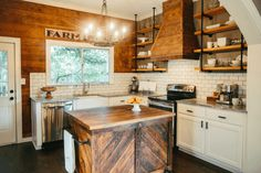 So much to love - painted white cabinets, subway tile, reclaimed wood island, butcher block, farmhouse sink, industrial-style pipe open shelving, that built-in range hood, black pulls and doorknob