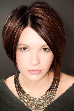 Les cheveux de cette femme ont été coiffés de façon à former une boule autour de sa tête. À remarquer aussi, la jolie raie quelque peu décentrée et la belle coloration brune éclaircie par des mèches cuivrées.