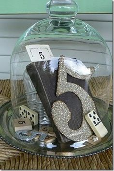 This is gorgeous table number centre piece, collect items with your table number and display them under a bell jar. A centre piece and table number all in one, if you placed it on a mirror and surrounding it with flowers or tealights, then you are pretty much done in terms of your central table decoration. #timelesstreasure