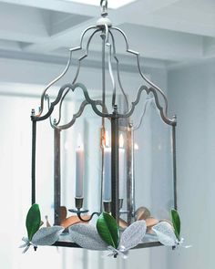 Just a few leaves -- some evergreen, some glimmering silver as if dusted with snow -- add subtle wintry beauty to a candlelit chandelier.