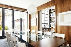 Modern and elegant dining space with modern light fixture and wood walls