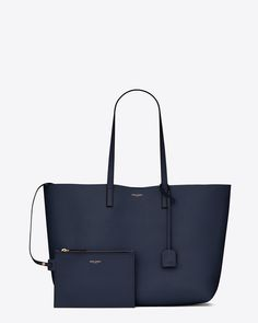 Shopping Saint Laurent E/W LARGE SHOPPING SAINT LAURENT TOTE BAG IN NAVY BLUE AND BLACK LEATHER $ 995.00 SAINT LAURENT UNSTRUCTURED TOTE BAG WITH CONTRASTING EDGES, FLAT LEATHER HANDLES AND REMOVABLE LEATHER ENCASED METAL INTERLOCKING YSL SIGNATURE CHARM. DIMENSIONS 14.4  10.9  5.1 INCHES
