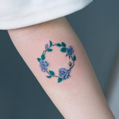 Blue rose wreath tattoo on the inner forearm.