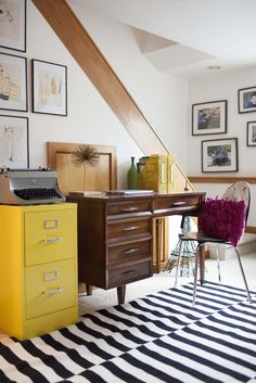 On the lower level of the home, at the base of the stairs, Audrey and Kevin have a work space.  Audrey's desk, file cabinet, typewriter, and even the vintage prints on the wall are all thrift store finds.