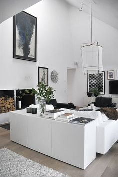 Gorgeous modern living room with black and white abstract art, paper pendant light and white console table.