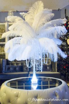 Hanging crystals or faux pearls from the feathers adds to the centerpiece decor | 15 Great Gatsby Party Ideas