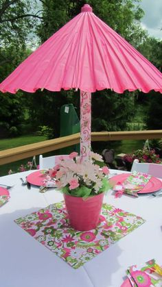 DIY umbrella centerpiece. Used umbrella from Hobby Lobby. Put into pole wrapped with any wrapping paper to match theme. Pink bucket also from H.L. Used wooden board and rocks inside to stabilize. Added floral foam and fresh flowers day of.