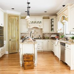 so much to love about this kitchen! Uneven cabinet heights, wood floors, furniture legs on cabinets, crown molding, light and bright!