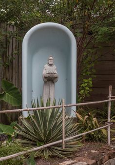 A shrine to St. Francis of Assisi, the patron saint of pets, was made using a clawfoot tub original to the home.