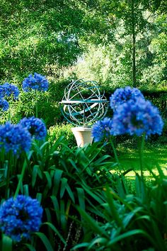 David harber sundials: Armillary sphere sundial on stone plinth with agapanthus in foreground