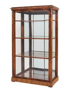 Biedermeier vitrine,  Ca. 1825/30. In walnut-veneered softwood with ¾ columns at the angles, glazing on three sides, 4 shelves and a mirrored back panel with glazing bars. 160 x 93 x 49 cm.